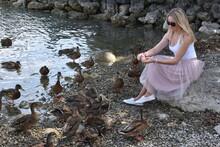 Full Length Of Woman Feeding Ducks On Shore At Beach