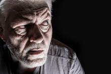 Porträt Von Einem älteren Mann, Der Skeptisch In Die Dunkelheit Blickt