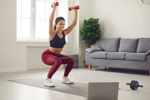 Home Online Workout In Front Of A Laptop With Dumbbells And Sports Rubber Bands. Woman Trains Squatting And Lifting Dumbbells Up Watching Online Broadcast Of Fitness Exercises Home Fitness Concept.