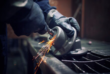 Factory Worker With Grinder Shaping Metal Components. Sparks Flying Around.