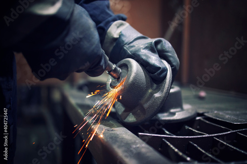 Obraz na płótnie Factory worker with grinder shaping metal components