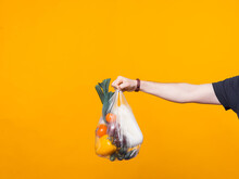 Photo Of A Mans Hand Holding A Pouch With Groceries Near A Yellow Wall .