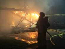 Firefighter Spraying Water On Burning Car
