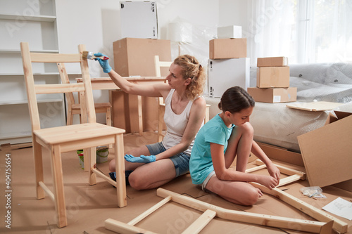 Obraz Mother and daughter painting and assembling furniture in new apartment, moving in and being hardworking. - fototapety do salonu