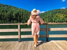 Back Of Woman Wearing Sun Hat With The Words Wish You Were Here Standing Near A Lake
