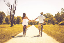 Romantic Couple In Love Cycling In The Park - Boyfriend And Girlfriend Holding Hands Travelling Together Outdoor - Vintage Filter
