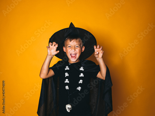 Portrait Of Boy Wearing Witch Costume Standing Against Yellow Background Fotobehang