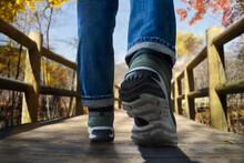 Low Section Of Man Walking On Footbridge During Autumn