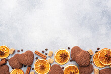 Chocolate Heart Cookies, Oranges Cinnamon And Spicy Spices On A Gray Table, Top View, Copy Space.