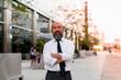 Leinwandbild Motiv Confident Asian businessman standing on the street