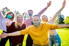 Happy Group Of Multiracial People Covered By Face Masks Having Fun Outside - New Normal Friendship Concept With Young Friends With Hands Up Outdoor