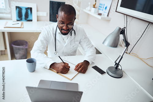 Cheerful doctor touching a sheet of paper with pencil Wallpaper Mural