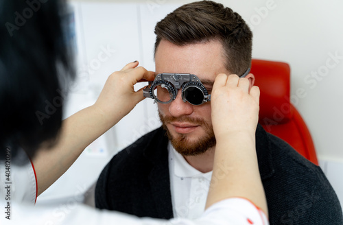 Male patient in ophthalmology clinic. Trial frame on handsome man`s eyes. Health check up in hospital.