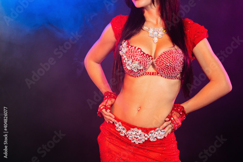 Obraz Midsection Of Sensuous Dancer In Red Costume Dancing Against Black Background - fototapety do salonu