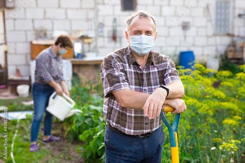Obraz na plátně Man professional horticulturist in protective mask with garden shovel working at