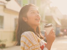 Young Woman Holding Disposable Coffee Cup On Street During Sunny Day