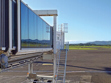 Exterior Of Passenger Boarding Bridge. Aircraft Access Walkway With Glass Tunnel. Aerobridge In Plane Parked In The Airport On Sunny Day. Jetway And Aeronautics Background.