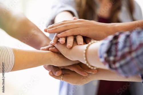 Fototapeta Young multiethnic friends stacking hands obraz
