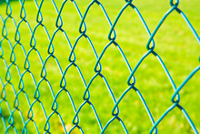 Green Metal Wire Mesh Against A Green Area Of A Public Park Or Private Property