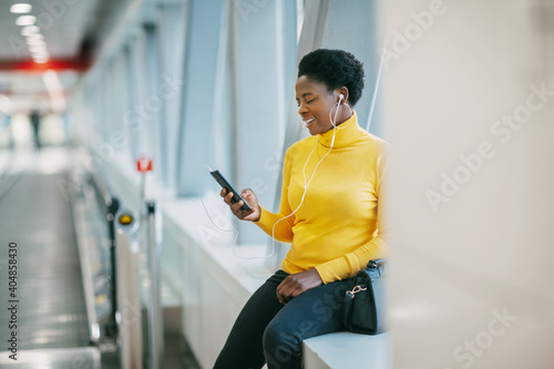 Fototapeta Attractive African girl is waiting for a train in the subway and listening to mu