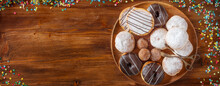 Various Carnival Donuts On A Wooden Table With Colorful Confetti. Horizontal Top View With Room For Text.