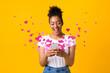 Leinwandbild Motiv Black woman sending love message on cellphone, hearts flying away