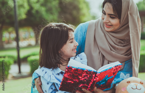 Obraz Mom and daughters spending time together at the park, in Dubai - fototapety do salonu