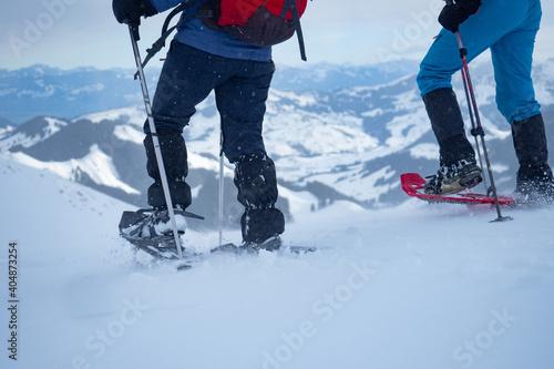 Billede på lærred Two snow shoe hikers walking down from Kronberg, a mountain in Switzerland