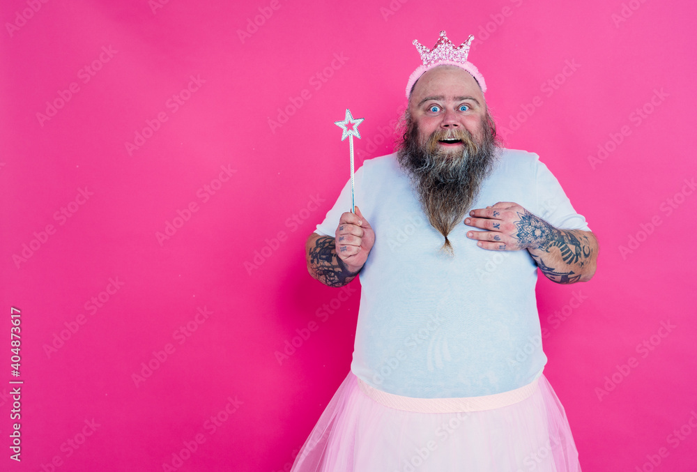Fototapeta Funny man dancing and having fun wearing  a ballet outfit. Happy princess on a pink colored background