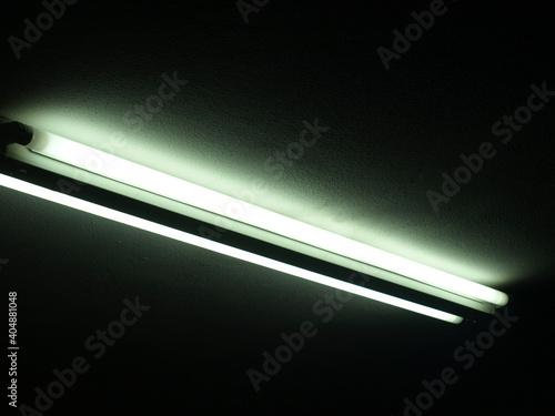 Obraz Lampa jarzeniowa na czarnym tle - fototapety do salonu