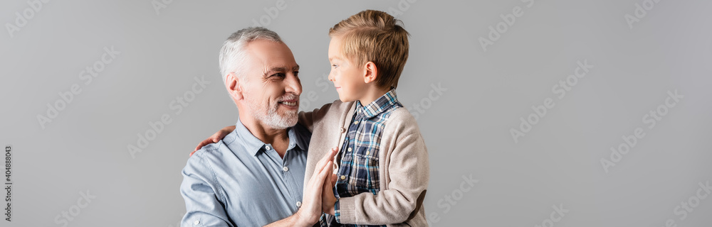 Fototapeta happy man giving high five to grandson while holding him isolated on grey, banner