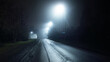 An empty old asphalt road in a fog at night. Street Lights close-up. Dark urban scene, cityscape. Riga, Latvia. Dangerous driving, speed, freedom, concept image