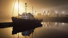 A Fishing Boat Moored To A Pier In A Fog At Night. Port Cranes In The Background. Yacht Club Illuminated By Lanterns. Reflections On The Water. Daugava River, Riga, Latvia
