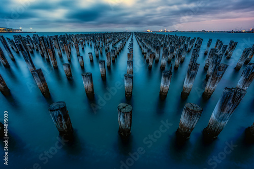 Fototapeta Wooden Posts In Sea Against Cloudy Sky During Sunset