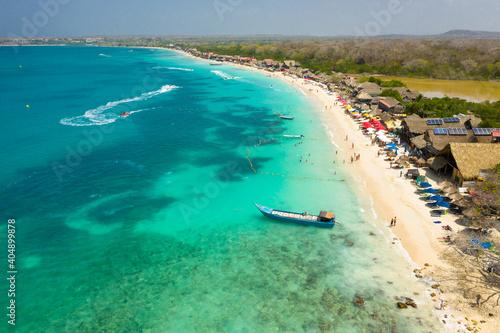 Fotografia Tropical sandy exotic emerald paradise beach with sunbeds and sun umbrellas aeri