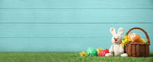 Colorful Easter Eggs, Basket And Bunny Toy On Green Grass Against Light Blue Wooden Background, Space For Text. Horizontal Banner Design
