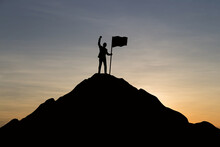 Silhouette Man Holding Flag While Standing On Mountain Against Sky During Sunset