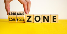 Comfort Or Learning Zone Symbol. Hand Turns Wooden Cubes And Changes Words 'comfort Zone' To 'learning Zone'. Beautiful Yellow Table, White Background, Copy Space. Business, Psychology Concept.
