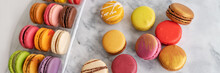 Many Macarons At Bakery In Gift Box. Panoramic Banner Of French Sweet Desserts Top View.