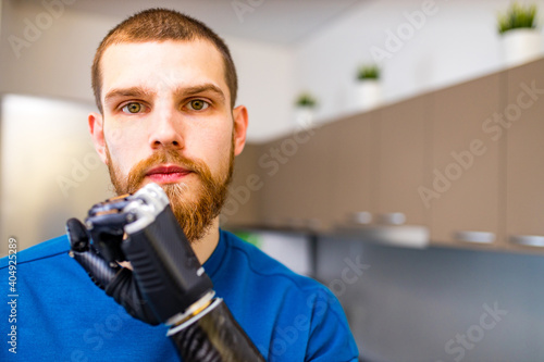 Fotografia young man with modern biotechnology hand in apartment