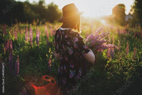 Stylish woman gathering lupine in wicker rustic basket in sunset light in field Fotobehang