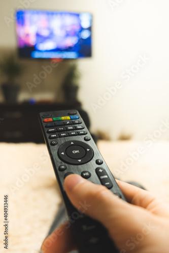 Obraz hand holding tv remote close-up - fototapety do salonu