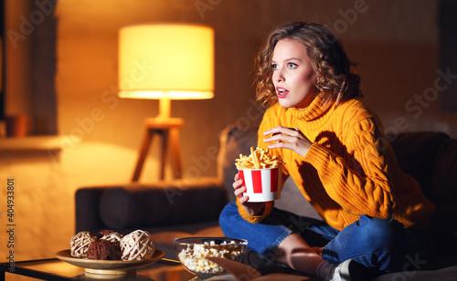 Slika na platnu Young female eating French fries and watching interesting movie