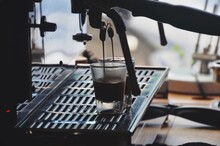 Close-up Of Coffee Maker Pouring Coffee Into Cup