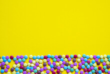 Colored Candy Border With Sugar Coated Chocolate Cuties On Light Blue Background With Copy Space