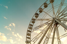 View From Below Of A Large Ferris Wheel In A Beautiful Sunset.