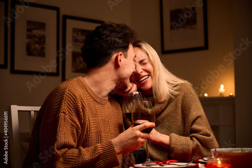 Obraz na plátně Happy young couple in love hugging, laughing, drinking wine, enjoying talking, having fun together celebrating Valentines day dining at home, having romantic dinner date with candles sitting at table