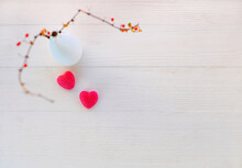 Holiday Background For Valentine's Day. Two Sweet Red Hearts And Abstract Branches Barberry On White Wooden Background. Copy Space, Selective Focus. Top View