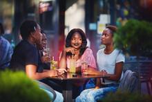 Beautiful African American Girls Talking, Sitting In Summer Cafe