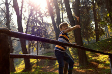 Playful Boy Throwing Leaves While Standing On Wooden Bridge In Nature.